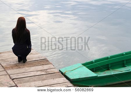 Young brunette girl waiting on a promontory