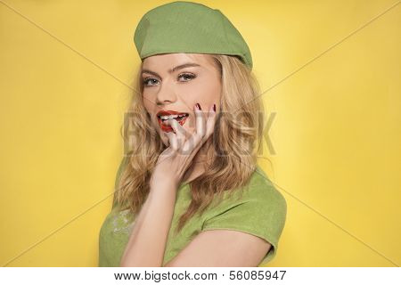 Beautiful young blond woman wearing a stylish green summer ensemble standing sideways looking at the camera with a pensive speculative look