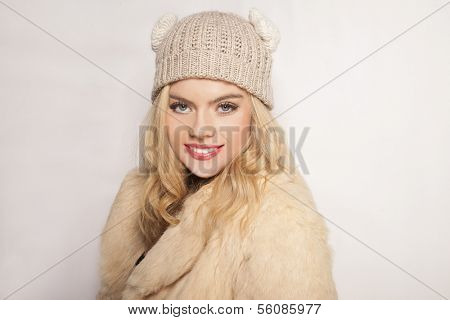 Beautiful blond girl in winter fashion wearing a warm wool overcoat and knitted beanie cap smiling at the camera, isolated on white