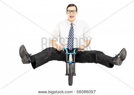 Excited young businessman with tie riding a small bicycle isolated on white background