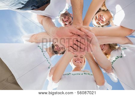 Low angle view of happy volunteers with hands together against blue sky