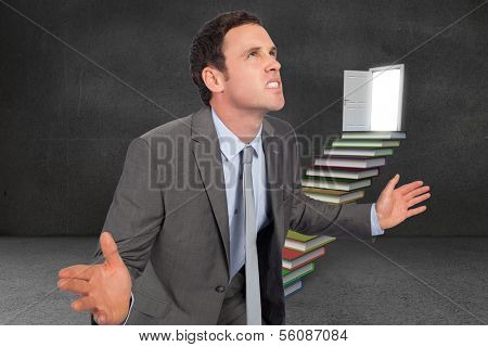 Businessman posing with hands out against steps made from books leading to door in grey room