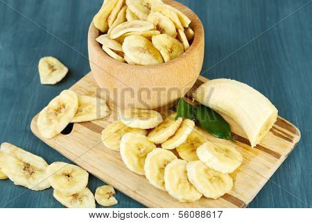 Fresh and dried banana slices  in bowl, on cutting board, on wooden background
