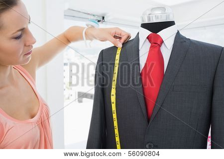 Side view of a female fashion designer measuring suit on dummy at office