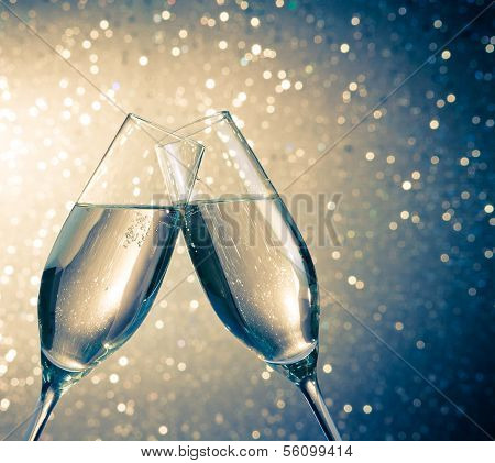 Champagne Flutes With Golden Bubbles On Blue Light Bokeh Background