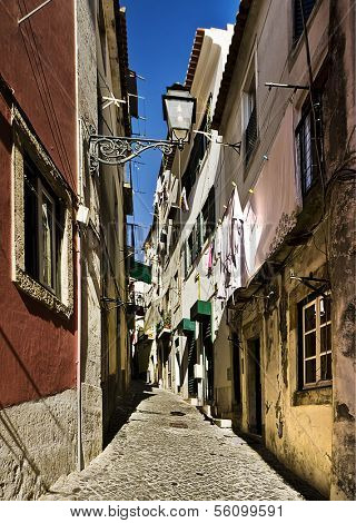 View of an old street with copperstones and colorful houses in Lisbon, Portugal