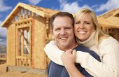 stock photo of excite  - Happy Excited Couple in Front of Their New Home Construction Framing Site - JPG