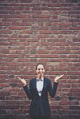 Image of impatient businesswoman with open palms on background of brick wall
