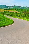 stock photo of plow  - Winding Paved Road between Spring Plowed Fields in the Tuscany - JPG