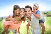 stock photo of piggyback ride  - Parents giving piggyback ride to kids - JPG
