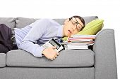 Exhausted young businessman sleeping on a couch with many document, isolated on white background
