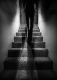 foto of paranormal  - Long exposure photograph of a a tall shadow figure walking up stairs - JPG