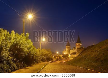 Night landscape with a road leading to the old fortress. Lamplight in the street. Historic Landmark. Old town of Kamenetz-Podolsk, Ukraine, Europe