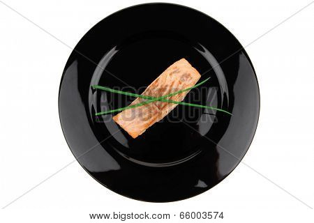 savory sea fish entree : roasted salmon fillet with green onion, on black dish isolated over white background