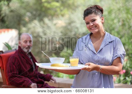 smiling home carer serving meal to elderly man