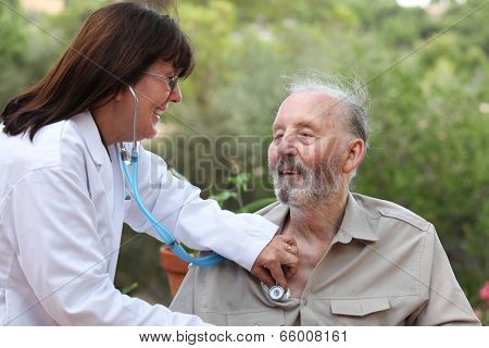 dr with stethoscope checking senior patients heat beat