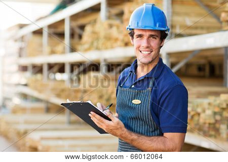 portrait of smiling industrial worker with clipboard