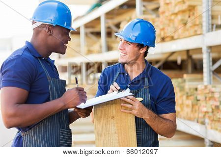 two male hardware store workers working in timber yard