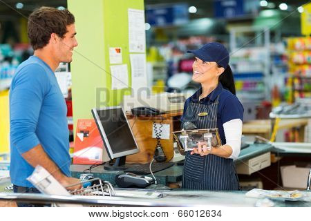 young man paying at till point in hardware store