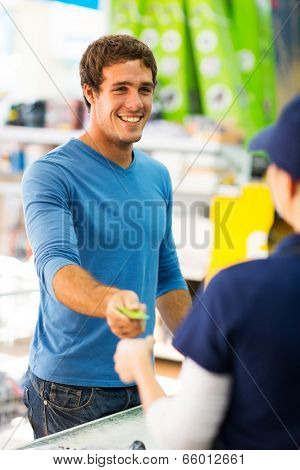 happy young man handing over credit card to a female cashier at till point