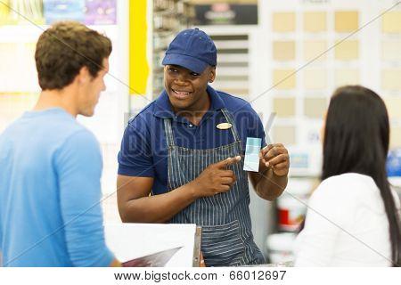 african paint store salesman helping couple choosing paint color