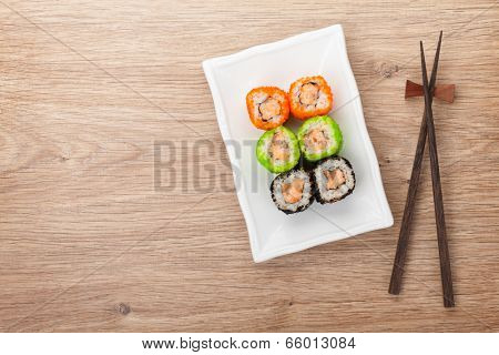 Sushi maki and chopsticks on wooden table. View from above with copy space