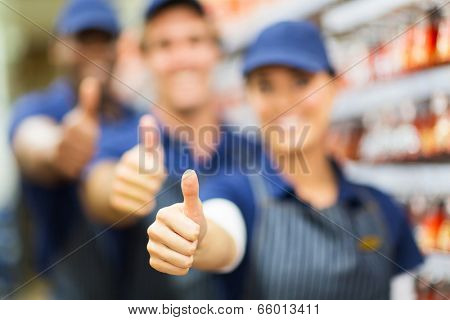closeup portrait of group of hardware store co-workers thumbs up