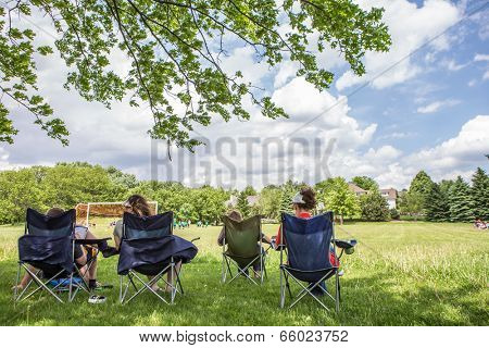 Parents sitting watching a childrens soccer game