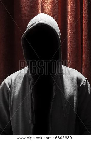 Portrait Of Invisible Man In The Hood With Red Curtain Background