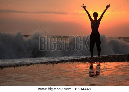 Silhouette Guy Lifted Hands Upwards On Sunset Wavy Beach