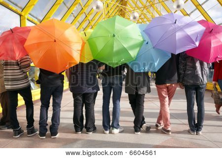 seven teens with opened umbrellas in pedestrian overpass. rainbow concept