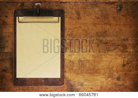 Antique clipboard on old grungy wooden surface, with plenty of copy space.