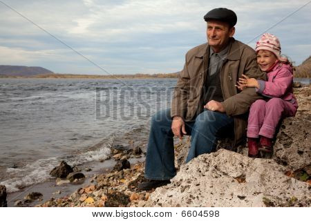 The grandfather and grand daughter sit on the stone near the lake