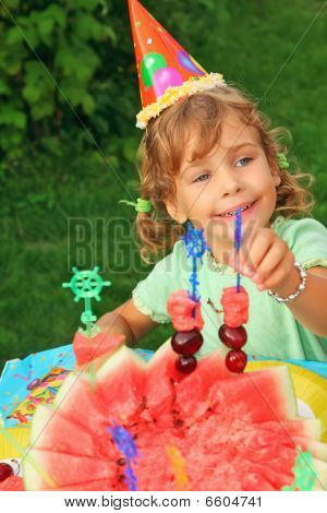 Little Girl In Cap Eats Fruit In Garden,happy Birthday