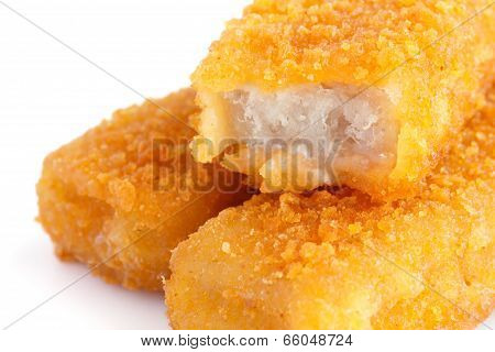 Fried fishfingers on white surface.