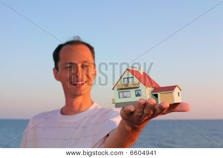 Young Man Keeps In Hand Model Of House With Garage