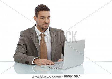 Young businessman sitting at desk using laptop computer.