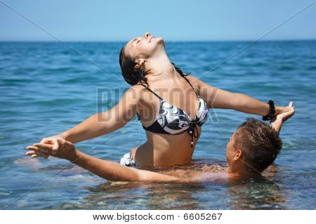 Young Hot Woman Sitting Astride Man In Sea Near Coast, Having Joined Hands