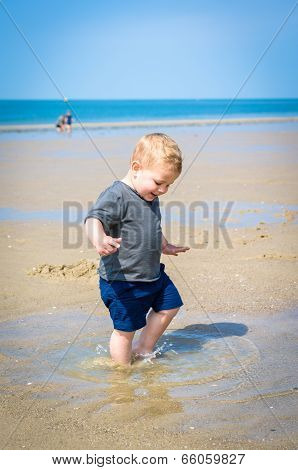Little Boy Splashes In A Pool On The Beach