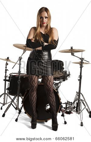 Young woman standing in front of drumkit on white background