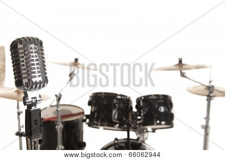 Close-up of microphone in front of Bass Drum Kit over white background