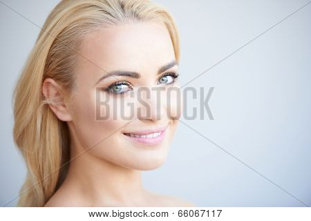 Beautiful blond woman with a lovely gentle smile looking sideways at the camera on a grey background with copyspace