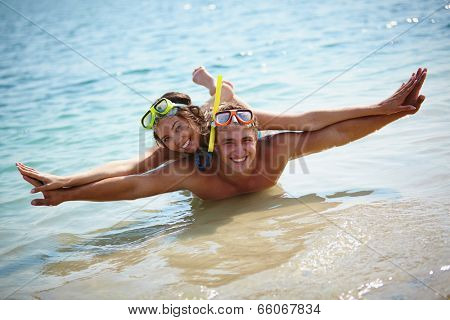 Couple of scubadivers looking at camera in water holding hands as if flying