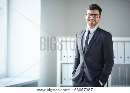 Handsome businessman in suit and eyeglasses looking at camera in office
