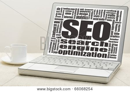cloud of words or tags related to SEO (search engine optimization) on a  laptop screen