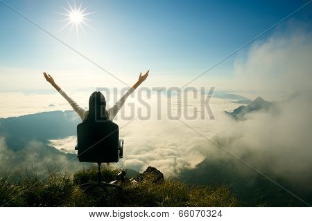 Young Woman Sits On A Chair And Open Her Arms At The Top Of The Mountain