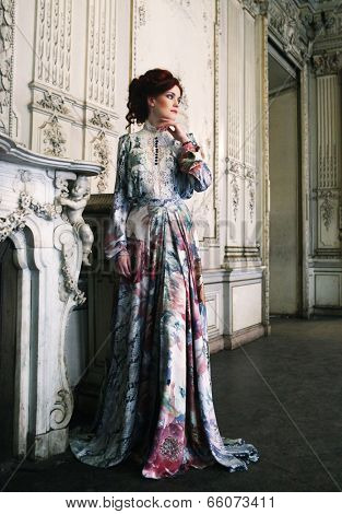 woman dressed in a dress in the palace posing next to the fireplace