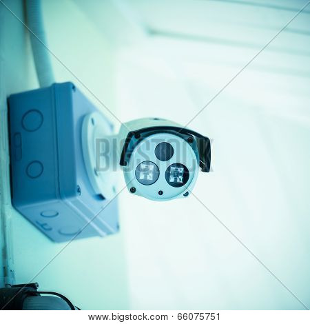 Cctv Camera On The White Wall With Blue Filter Effect.