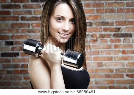 Young Smiling Woman Lifting Dumbbells
