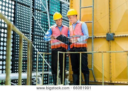 Asian Indonesian construction workers with helmet and safety vest on a building or industrial site in Asia